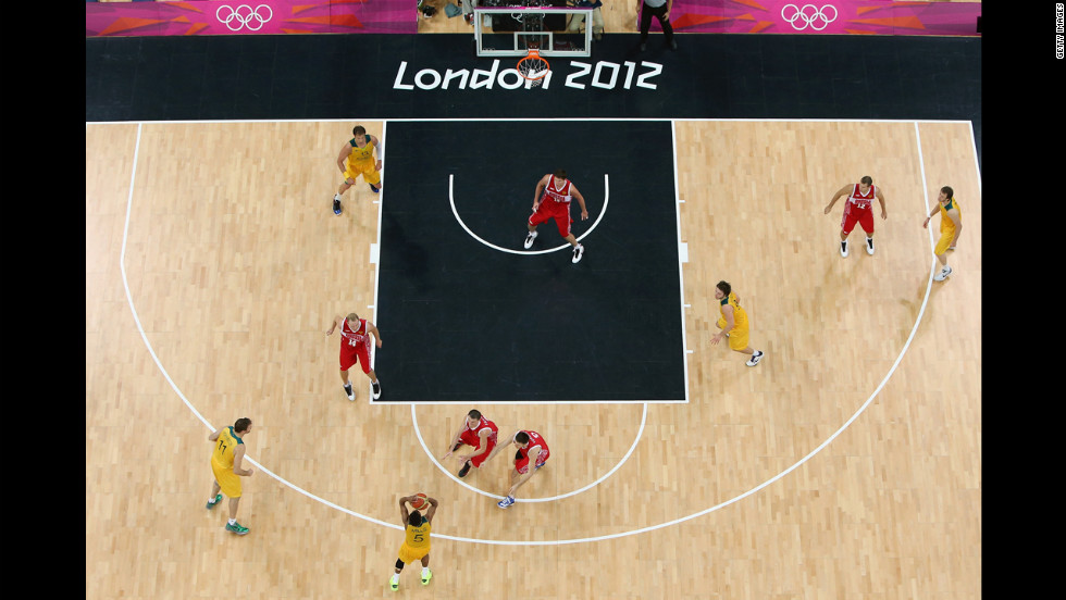 Australia, in yellow, and Russia face off in the final seconds of the men's basketball preliminary round match.