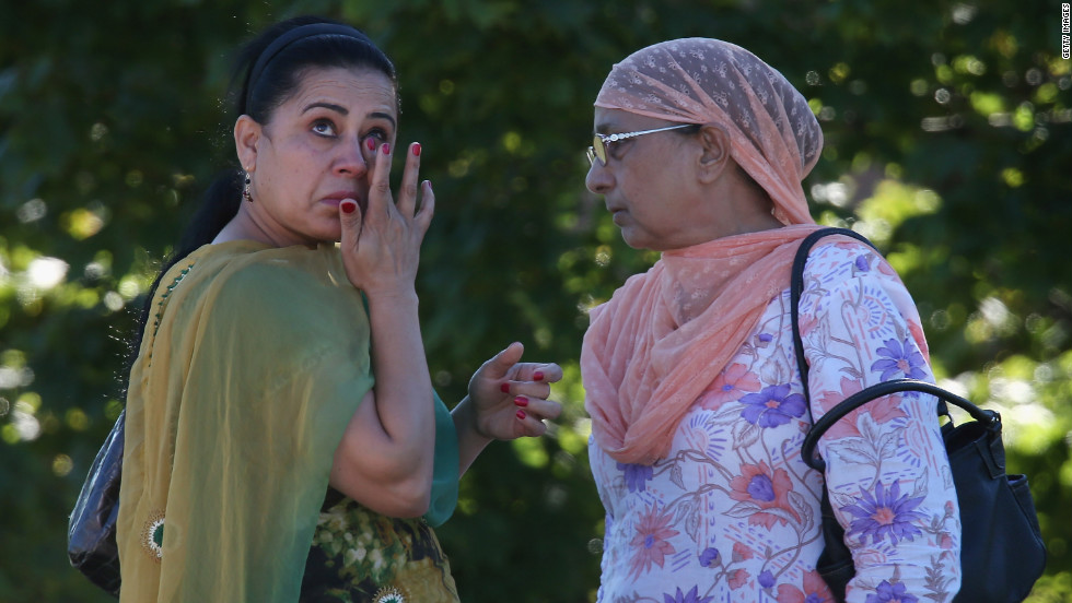 A woman wipes away a tear outside the Sikh temple.