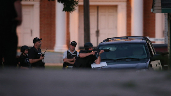 Officers take cover behind a vehicle as they secure the neighborhood where the shooter is believed to have lived in Cudahy, Wisconsin.