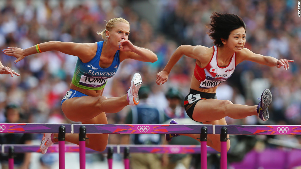 Marina Tomic, left, of Slovenia and Ayako Kimura of Japan compete in the women's 100-meter hurdles Monday.
