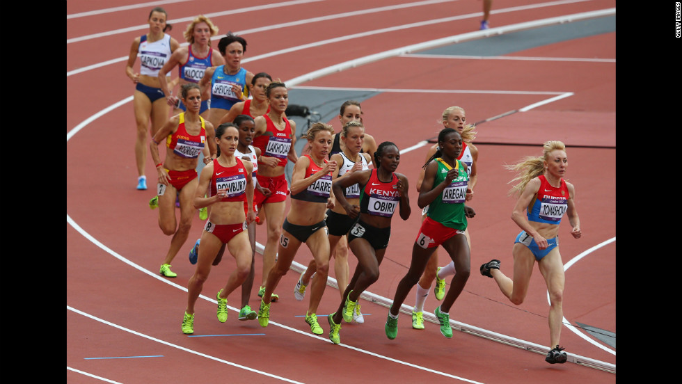 Runners round a turn in the women's 1,500-meter heat Monday.