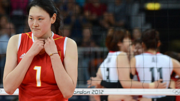 Chinese volleyball player Wang Yimei reacts as the Japanese team celebrates after it won the third set women