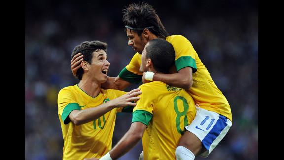 Brazil midfielder Oscar, left, and Brazil forward Neymar, right, congratulate goal scorer Brazil defender Romulo, second right, during the London 2012 Olympic men