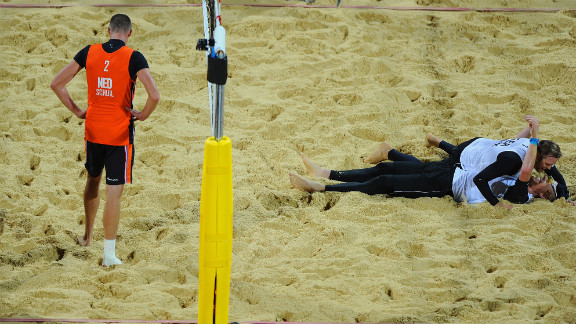 Rich Schuil of Netherlands looks dejected as Julius Brink and Jonas Reckermann of Germany celebrate match point during the men