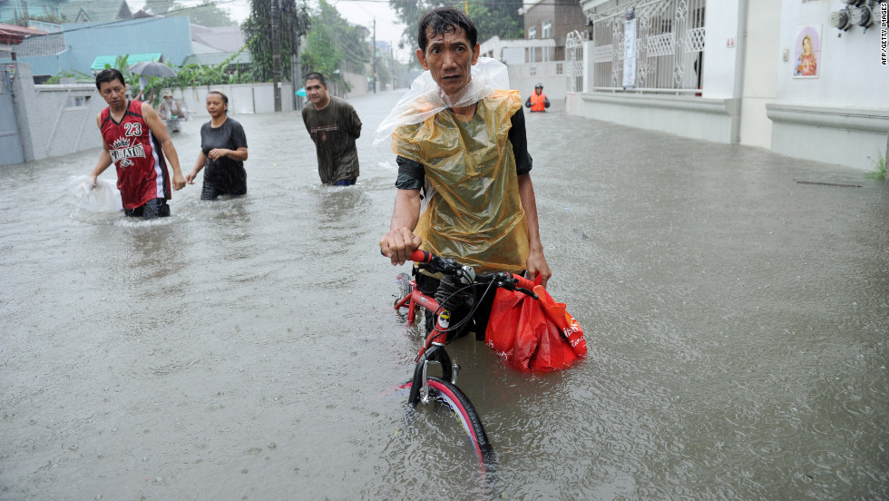 A resident pushes his bicycle through floodwaters in Quezon City in suburban Manila.