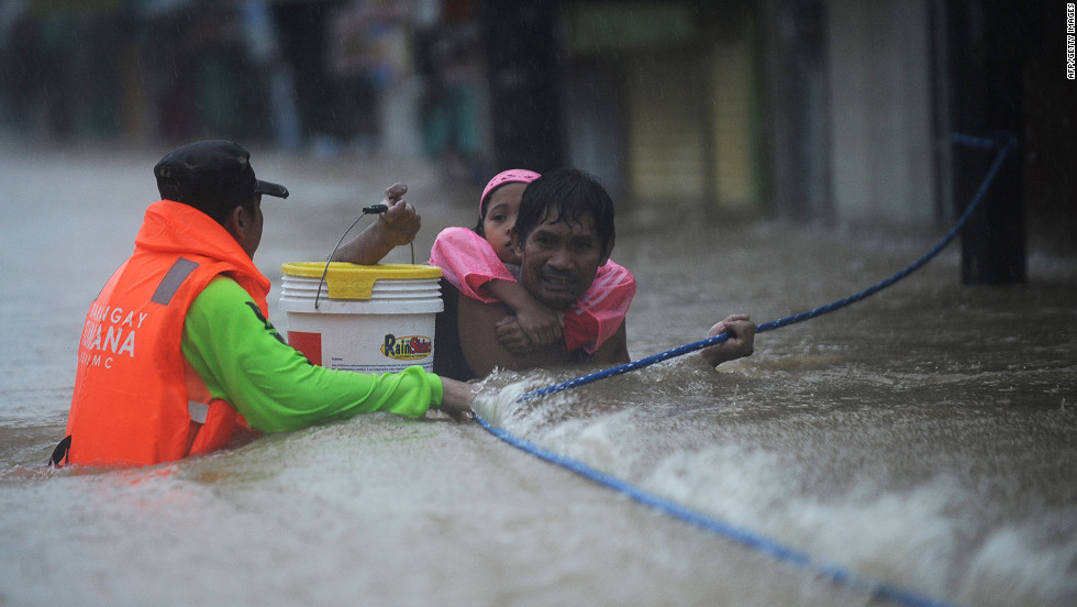 A rescuer guides a man carrying his daughter on his back through a strong current.