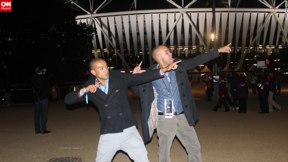 Two spectators outside the Olympic Park do their best Usain Bolt salutes.