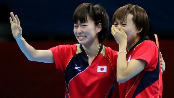 Japanese table tennis players Kasumi Ishikawa, left, and Sayaka Hirano weep after beating Singapore in the women