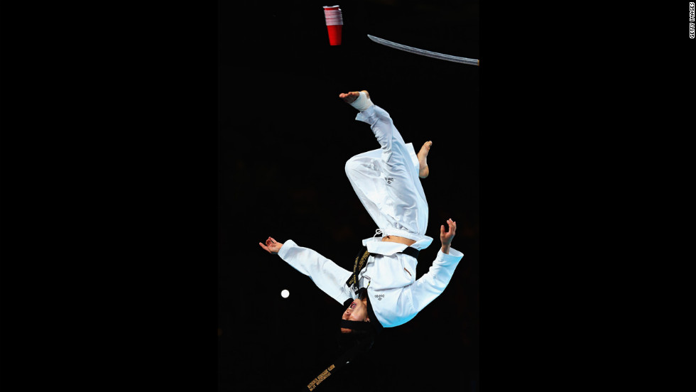 A martial arts specialist performs stunts before the night session of taekwondo.