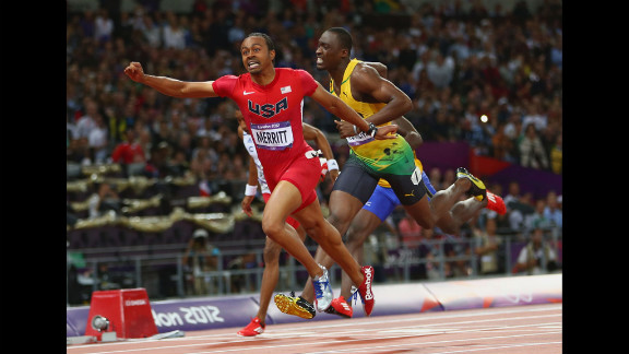 Aries Merritt of the United States crosses the finish line ahead of Hansle Parchment of Jamaica to win gold in the men