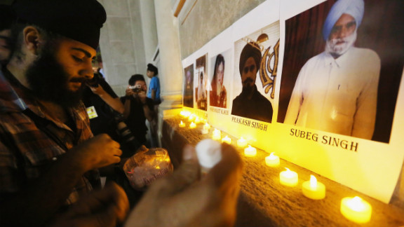 Photos of the victims are displayed during a candlelight vigil Wednesday in New York