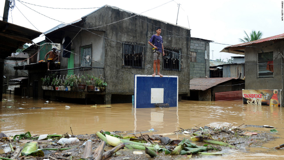 A boy stands on a basketball backboard among flooded homes in San Mateo, Rizal.