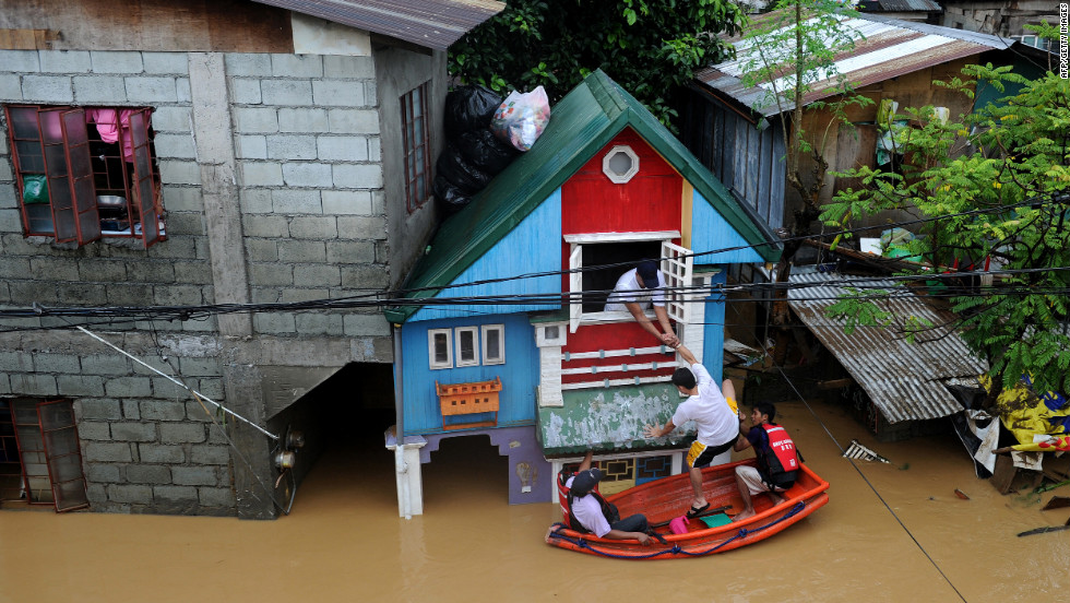 Rescue workers help people return to their home near a river that overflowed in the Manila suburb of San Mateo, Rizal.