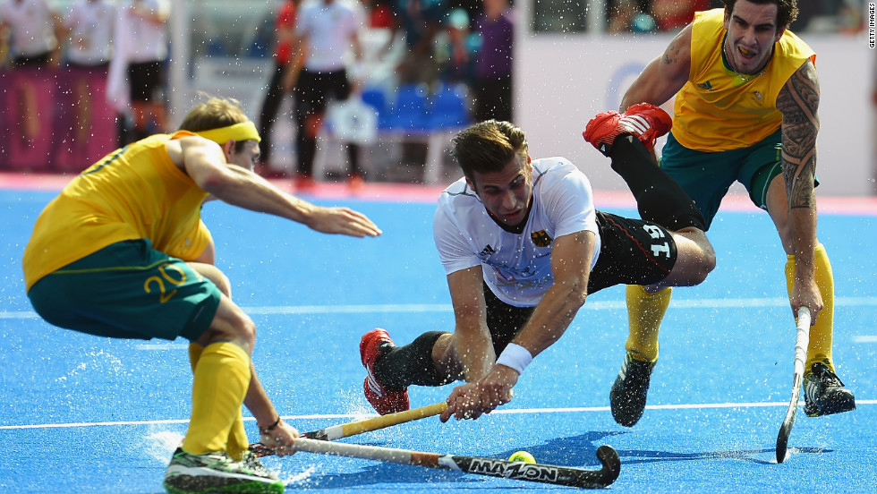 Germany's Christopher Zeller, center, competes with Australia's Matthew Swann, left, and Kieran Govers during the men's field hockey semifinal match.