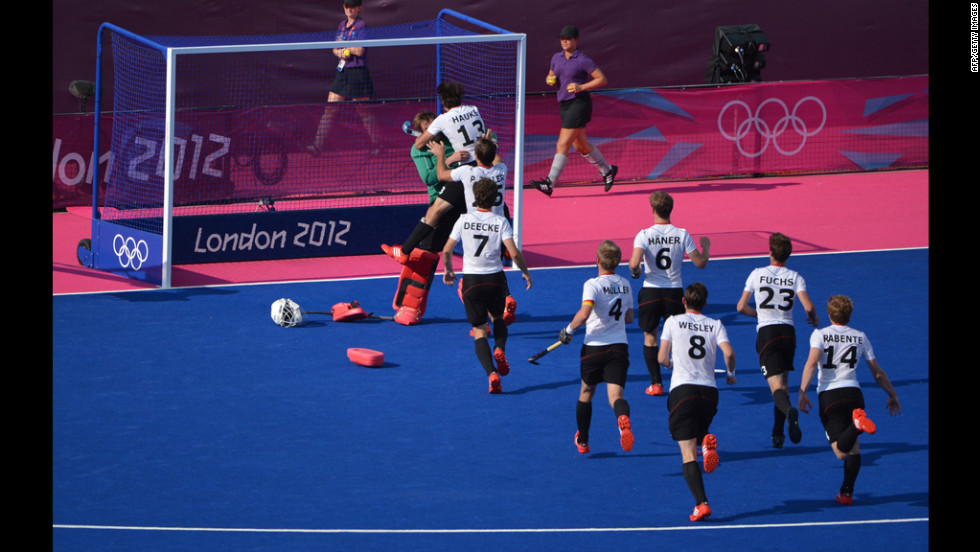 The German team runs toward goalkeeper Max Weinhold after winning the men's field hockey first semifinal against Australia.