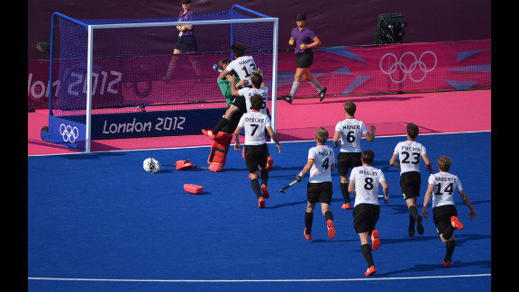 The German team runs toward goalkeeper Max Weinhold after winning the men