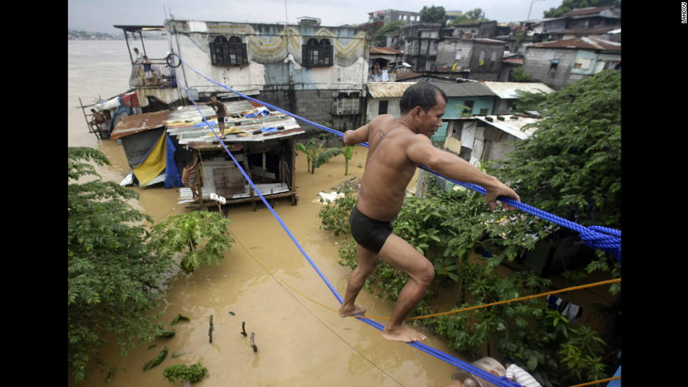 A man crosses the floodwaters on a rope in Pasig City, east of Manila, on Thursday, August 9.