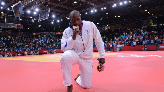 Gold medalist France's Teddy Riner bites his medal after winning a judo event.