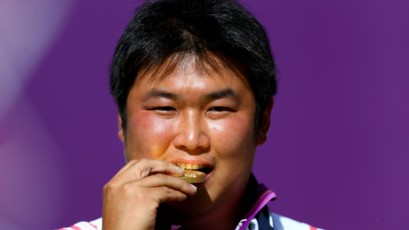Oh Jin-hyek of South Korea bites his gold medal after winning an archery competition.
