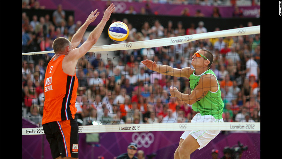 Martins Plavins of Latvia, right, hits a return against Rich Schuil of Netherlands during the men's beach volleyball bronze medal match.
