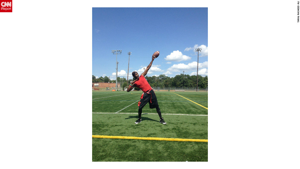 "Tariq Rasheed Ali, a ""huge Usain Bolt fan"" and a personal trainer, strikes the Bolt pose at Virginia Tigers full contact flag football practice at Bryant Alternative High School in Alexandria, Virginia."