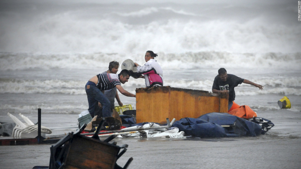 People try to recover belongings being washed away by the flood in Boca Del Rio on the outskirts of Veracruz on Thursday, August 9. Tropical Storm Ernesto skirted the coast of the Gulf of Mexico on Thursday, sending wind gusts and showers across the state of Veracruz, home to some of Mexico's busiest ports and oil installations.