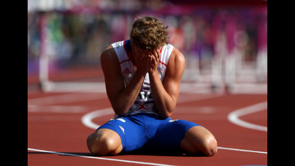 Kevin Mayer of France sits on the track after finishing last in heat 3 of the men