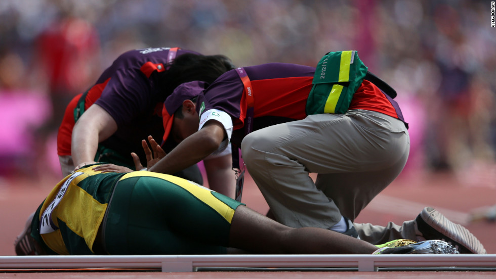 Ofentse Mogawane of South Africa receives assitance after colliding with a Kenyan runner during the men's 4 x 400-meter relay round 1 heats.
