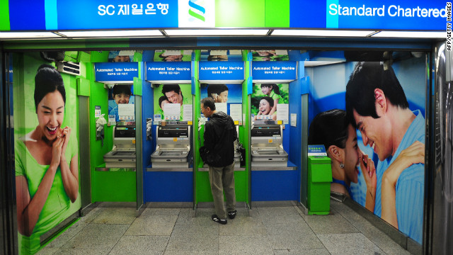 A man uses an automated teller machine of SC First Bank at a subway station near the bank's headquarters in Seoul on June 27, 2011.