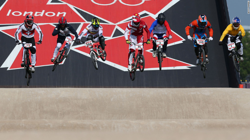 Cyclists race down the starting ramp in the  in the men's BMX cycling final.