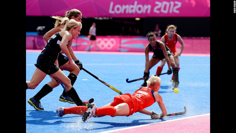No. 15 Alex Danson of Great Britain, right, battles for the ball against No. 2 Emily Naylor, front, and Clarissa Eshuis No. 16 of New Zealand during the first half of the women's hockey bronze medal match.