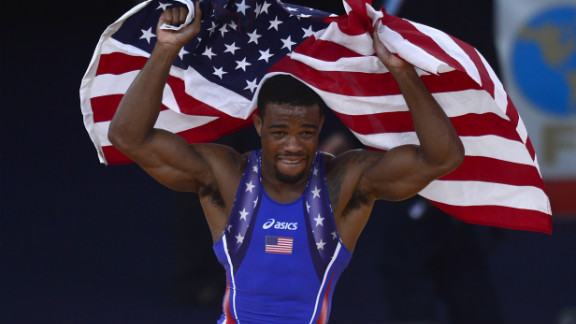 U.S. wrestler Jordan Ernest Burroughs celebrates with the national flag after defeating Iran