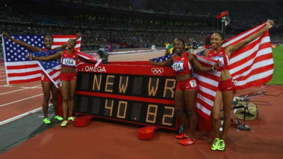Carmelita Jeter, Bianca Knight, Allyson Felix and Tianna Madison of the United States celebrate next to the clock after winning gold and setting a new world record of 40.82 seconds in the women