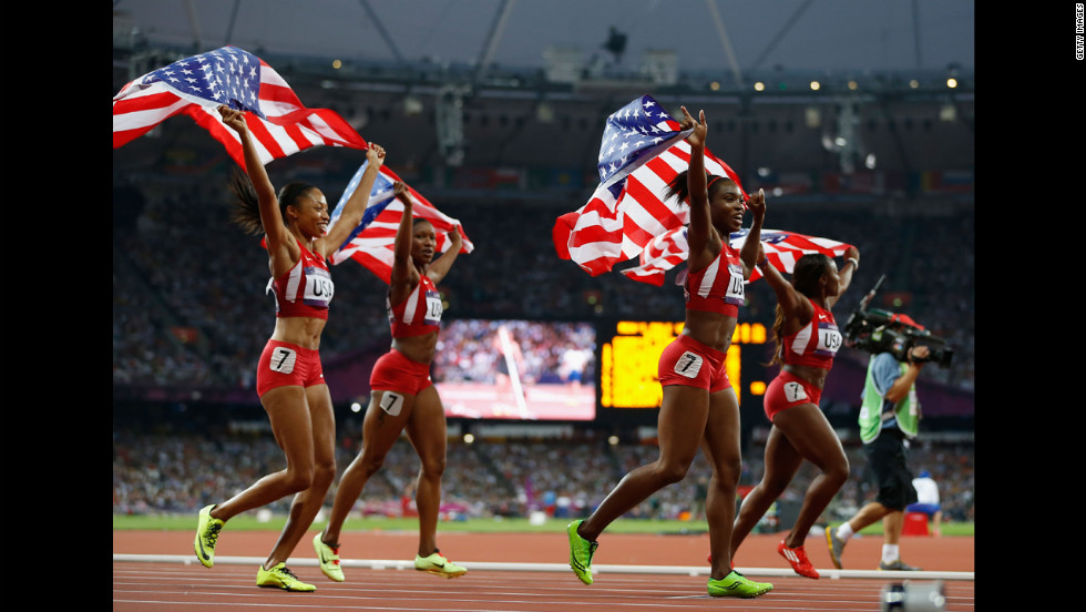 The U.S. women's 4x100-meter relay team wave the flag to celebrate their world record and gold medal winning victory.