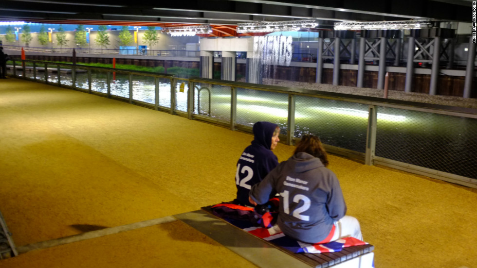 "Two Eton Manor volunteers took a moment for a quiet conversation in front of the ""bit.fall"" installation by artist Julius Popp. Words taken from live news headlines are projected at random onto five man-made waterfalls under the Stratford Gate bridge."