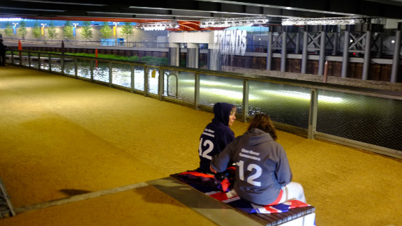 """Two Eton Manor volunteers took a moment for a quiet conversation in front of the """"bit.fall"""" installation by artist Julius Popp. Words taken from live news headlines are projected at random onto five man-made waterfalls under the Stratford Gate bridge."""