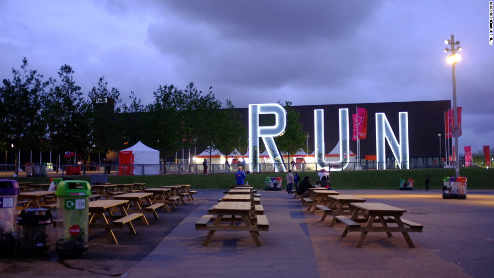 "The picnic area outside the Copper Box, crowded earlier in the day, was almost deserted at dusk. Artist Monica Bonvicini's permanent sculpture, ""Run,"" shone brightly in front of it. The venue will become a multi-purpose venue for community and sporting events."