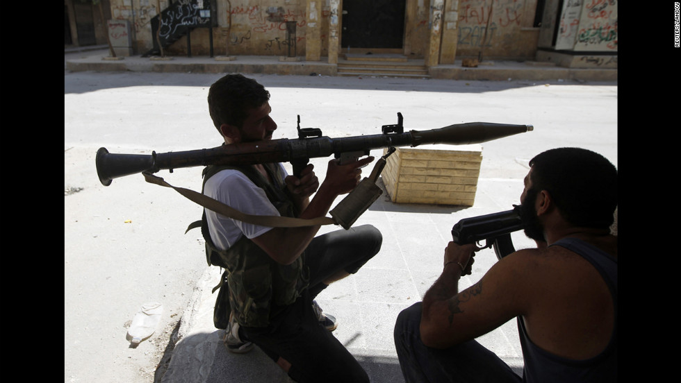A Free Syrian Army fighter aims an RPG as he waits for Syrian army tanks in the Salaheddine neighborhood.