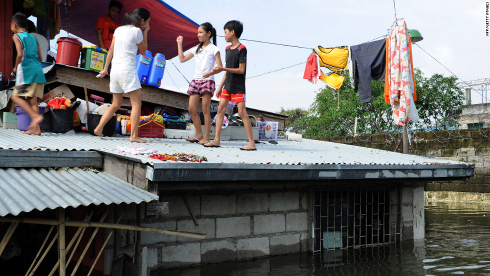 A family gathers on the roof of a home in Calumpit town, north of Manila.