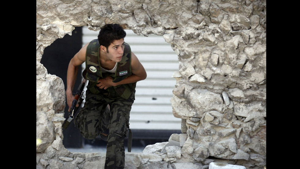 A Free Syrian Army fighter runs for cover during heavy fighting in the Salaheddine neighborhood.