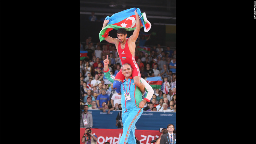 Azerbaijan's Toghrul Asgarov celebrates with his coach after defeating Russia's Besik Kudukhov in a men's freestyle wrestling gold medal match.