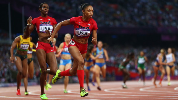 Allyson Felix receives the relay baton from DeeDee Trotter during the women