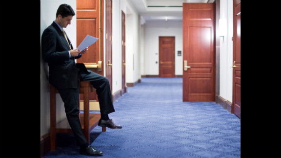 Ryan looks over papers as he waits for other House Republicans to arrive for a news conference in the Capitol Visitors Center in 2010.