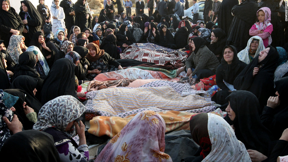 Bodies recovered from the rubble lie covered as villagers mourn their deaths.