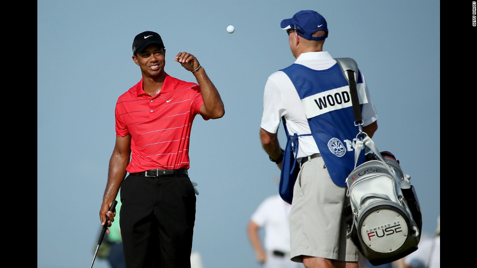 Woods catches a ball tossed by caddie Joe LaCava on the 14th green.