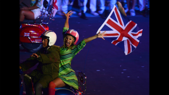 Actors ride scooters during the closing ceremony.