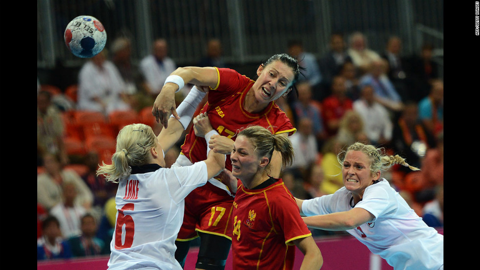 Montenegro's Bojana Popovic, top, shoots over Norway's pivot Heidi Loke, left, during the women's gold medal handball match between Norway and Montenegro.