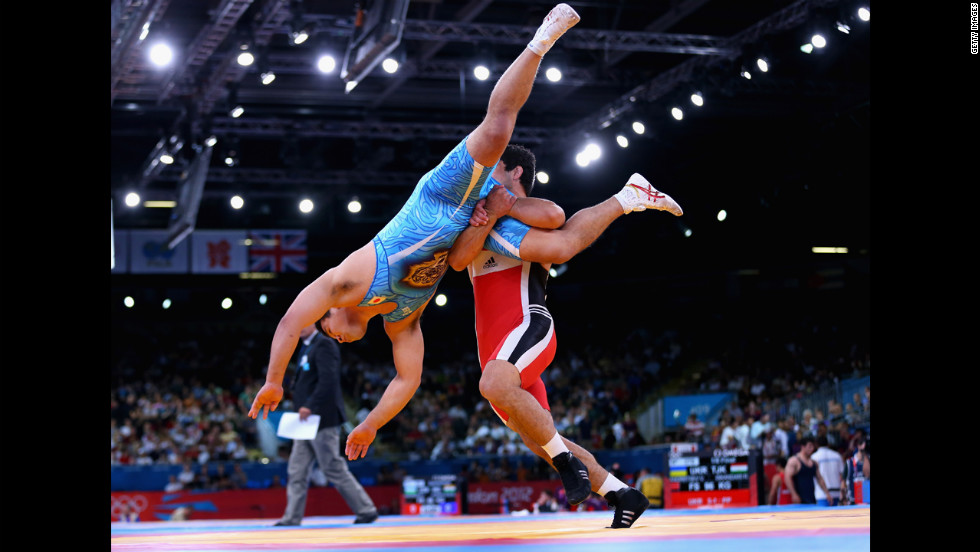 Takao Isokawa, in blue, of Japan is taken down by Magomed Musaev of Kyrgyzstan in the men's freestyle wrestling 96-kilogram eighth-final match.