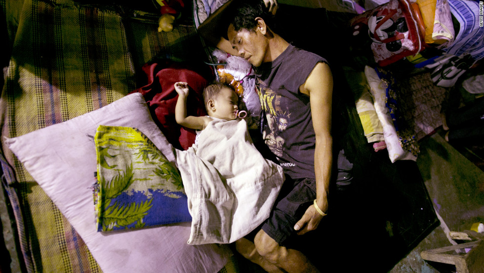Displaced flood victims sleep at a crowded evacuation shelter in Manila on Monday, August 13.