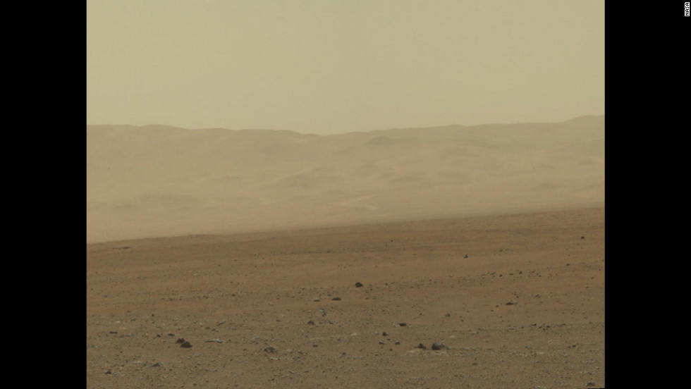 "In this portion of the larger mosaic from the previous frame, the crater wall can be seen north of the landing site, or behind the rover. NASA says water erosion is believed to have created a network of valleys, which enter ""Gale Crater"" from the outside here."